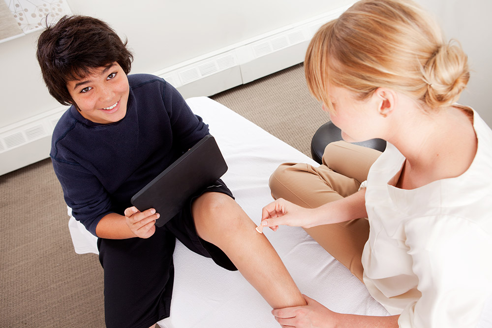 Young male receiving pediatric acupuncture while playing games on a digital tablet